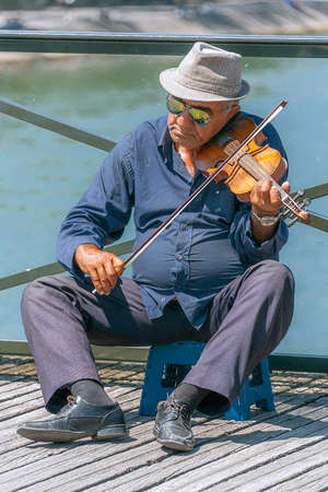 Paris, France - July 4, 2017: Old man on a stool playing violin for tips on Pont des Arts pedestrian bridge over River Seine in Paris, once known as The Love Lock Bridge. Editorial