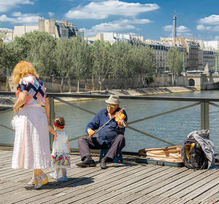 Paris, France - July 4, 2017: Old man on a stool playing violin as tourists passing by for tips on Pont des Arts pedestrian bridge over River Seine in Paris, once known as The Love Lock Bridge.