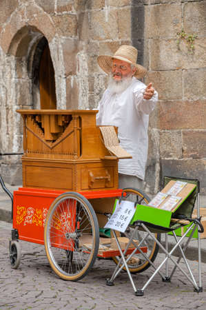 Saint-Malo, France - July 20, 2017: An old man with long white bread stands behind his street organ chanting and singing while playing his musical instrument for tips.