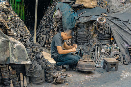 Bangkok Noi, Bangkok - September 28, 2019: Street scrap yard worker. A worker dismantles an engine into pieces to sell as spare parts with mountain of engine pieces surrounding him.