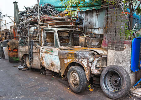 Wrecked pickup truck with pieces of used spare parts on its top, left abandoned along alleyway. Stock Photo - 133076152