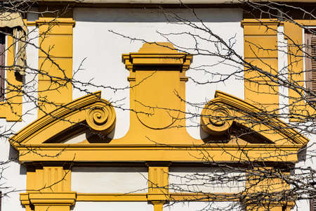 Yellow pediment over a doorway in curved and broken-apex style. The opening in the middle is facial-like molding which resembles a person flexing his arm muscles.
