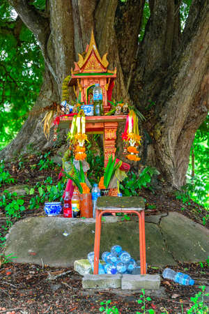 A spirit house on earth mound with a huge tree stands behind. Traditional Thai Miniature house built for a guardian spirit to reside. Food and drink are common offerings from Buddhists and worshipers.