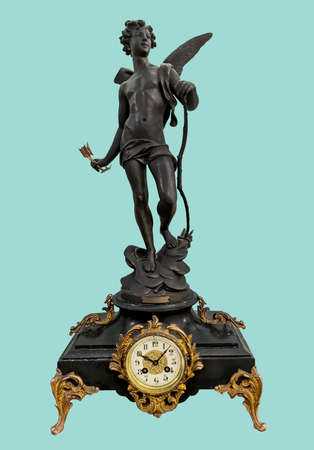 Antique mantel clock with Eros statuette in basalt black holding bow and arrow, on isolated green background