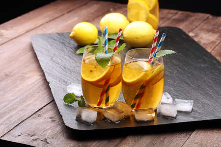 Iced tea with lemon slices, mint and ice on rustic background