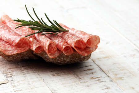 longaniza: thinly sliced salami on a wooden texture on the background