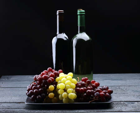 Bottle of white wine, grape and corks on wooden table Stock Photo