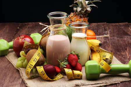 fitness equipment and healthy food - Strawberry Banana smoothie or milkshake(green apple, pepper, grapes, nectarines, kiwi, orange, dumbbells and measuring tape) Stockfoto