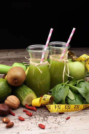 Healthy green smoothie and ingredients - superfoods, detox, diet, health, vegetarian food concept, fitness equipment and green apple, dumbbells and measuring tape