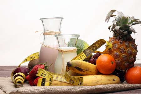 fitness equipment and healthy food - Strawberry Banana smoothie or milkshake(green apple, pepper, grapes, nectarines, kiwi, orange, dumbbells and measuring tape) Stock Photo