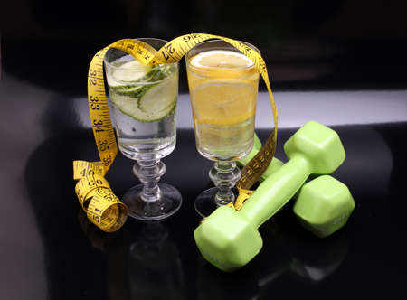fitness equipment and healthy food and detox water (green apple, pepper, grapes, nectarines, kiwi, orange, dumbbells and measuring tape)