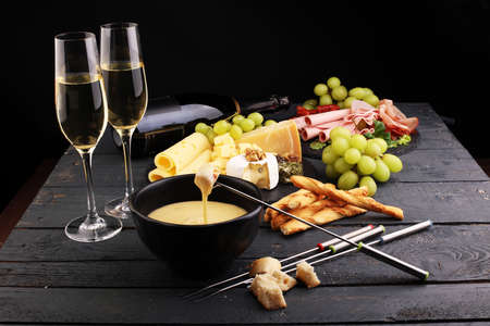 Gourmet Swiss fondue dinner on a winter evening with assorted cheeses on a board alongside a heated pot of cheese fondue with two forks dipping bread and white wine behind in a tavern or restaurant Stockfoto