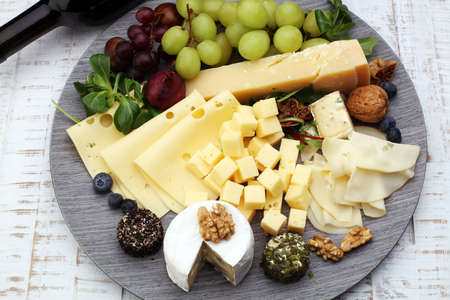 Cheese platter with different cheese and grapes and red wine Stock Photo