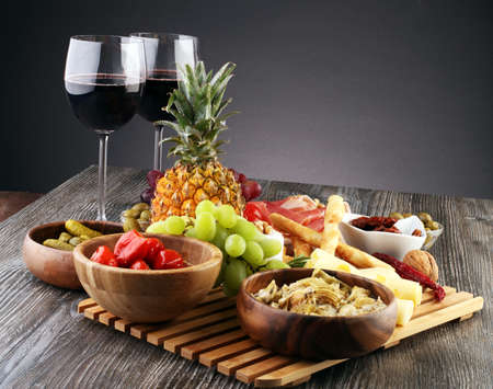 Italian antipasti wine snacks set. Cheese variety, Mediterranean olives, pickles, Prosciutto di Parma with melon, wine in glasses over black grunge background