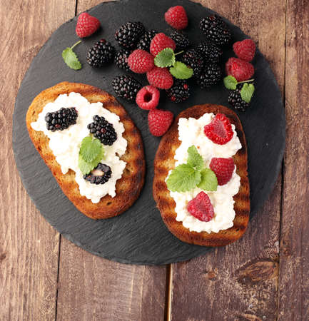 time sharing: Bread with cheese cream and blackberries and raspberries for lunch table. Sharing antipasti on party or summer picnic time over wooden rustic background.