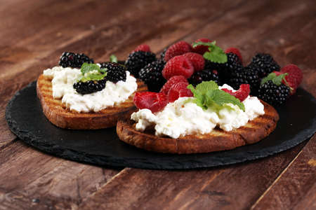 Bread with cheese cream and blackberries and raspberries for lunch table. Sharing antipasti on party or summer picnic time over wooden rustic background.