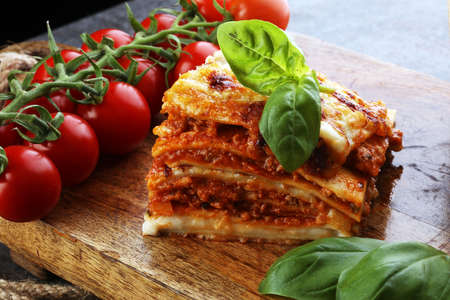 Serving of spicy traditional Italian beef lasagne in a restaurant - bolognese sauce