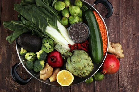 Vegetables, fruit, seeds, cereals, beans, spices, superfoods, herbs, condiment in silver pan for vegan, gluten free, allergy-friendly, clean eating and raw diet.
