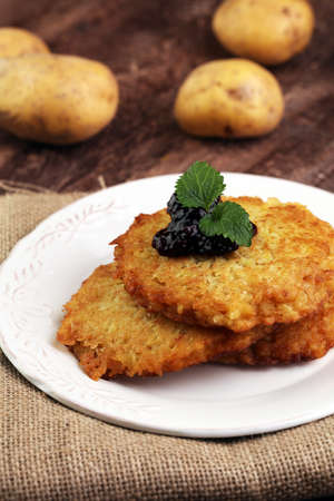 Potato pancake with cow berry sauce, selective focus Stock Photo