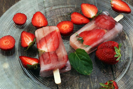 Healthy strawberry popsicles with fresh slices on wooden background