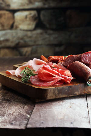 Marble cutting board with prosciutto, bacon, salami and sausages on wooden background. Meat platter Archivio Fotografico