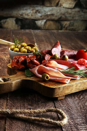 Marble cutting board with prosciutto, bacon, salami and sausages on wooden background. Meat platter Stockfoto