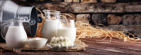productos lacteos. sabrosos productos lácteos saludables en una mesa en. crema agria en un tazón, tazón de queso cottage, crema en un banco y tarro de leche, botella de vidrio y en un vaso