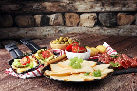 맛있는 스위스 치즈가 삶은 또는 구운 감자에 녹인 라클레트 치즈를 살라미 소시트 프라이팬에 담았습니다.