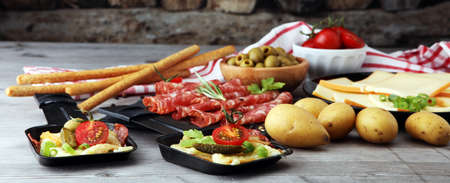 Delicious traditional Swiss melted raclette cheese on diced boiled or baked potato served in individual skillets with salami.