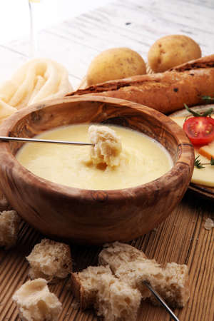 Gourmet Swiss fondue dinner on a winter evening with assorted cheeses on a board alongside a heated pot of cheese fondue with two forks dipping bread and white wine behind in a tavern Stock Photo