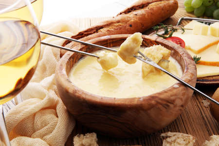 Gourmet Swiss fondue dinner on a winter evening with assorted cheeses on a board alongside a heated pot of cheese fondue with two forks dipping bread and white wine behind in a tavern Foto de archivo