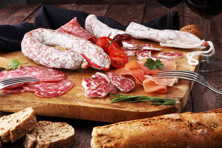Wooden cutting board with prosciutto, salami, sausages, wine, bread  and  rosemary Stockfoto