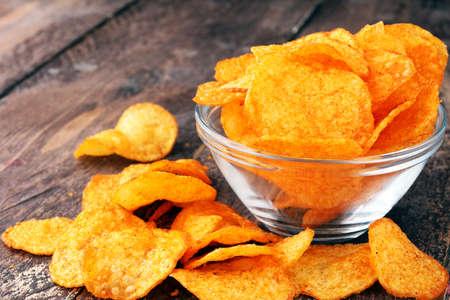 Crispy potato chips in a bowl. Tasty paprika chips.