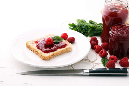 Fresh raspberry jam with toast or bread for breakfast.