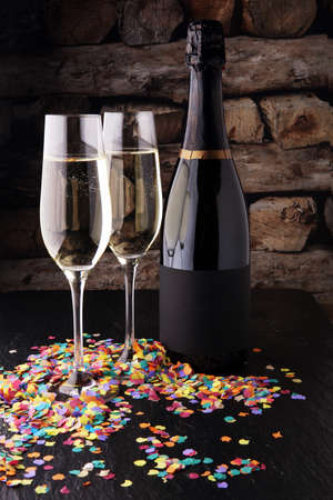 New Year concept with champagne in glass and bottle and confetti