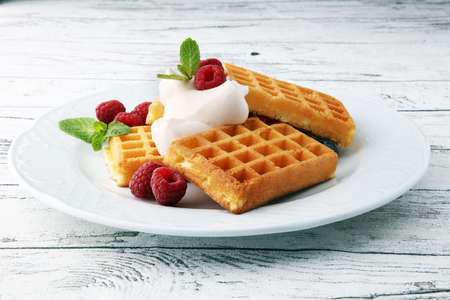 Plate of belgian waffles with whipped cream, mint and fresh berries