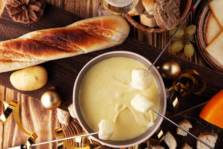 Gourmet Swiss fondue dinner on a winter evening with assorted cheeses on a board alongside a heated pot of cheese fondue with two forks dipping bread and white wine behind in a tavern or restaurant. Banque d'images