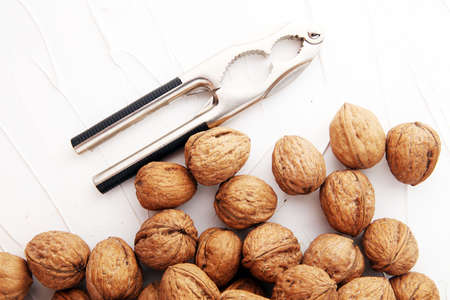 Walnut kernels and whole walnuts on table with a nutcracker Archivio Fotografico