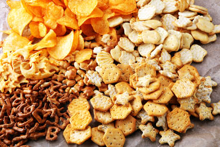 Salty snacks. Pretzels, chips, crackers on brown wooden backgroun d