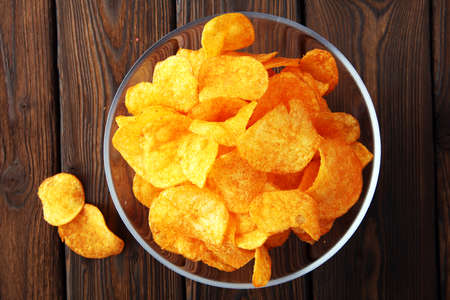 Crispy potato chips. Paprika chips on wooden background. Stock Photo