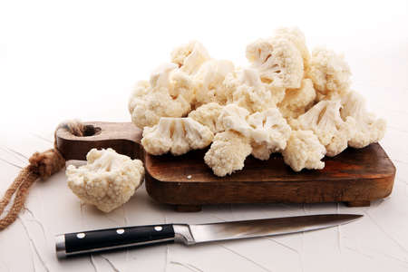 Fresh organic cauliflower cut into small pieces on cutting board Stockfoto