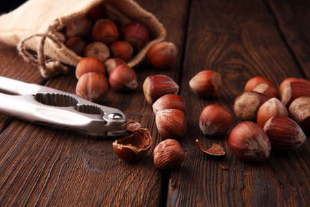 Hazelnut with peeled hazelnuts in burlap on textured wooden background