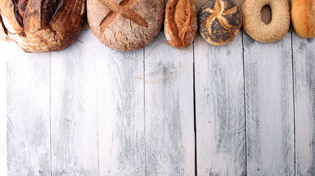 Different kinds of bread and bread rolls on wooen backgroundKitchen or bakery poster design