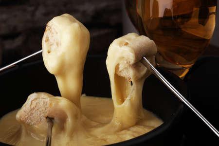 冬の夜のグルメスイスフォンデュディナーは、チーズフォンデュの加熱ポットと一緒に、2つのフォークがパンと白ワインまたはシャンパンを浸すボ