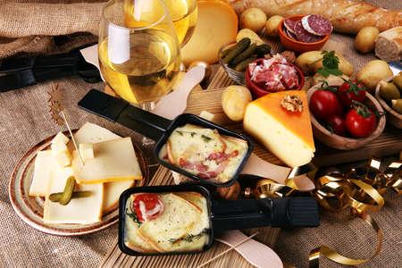 おいしい伝統的なスイスの溶かしたラクレットチーズは、個々のフライパンで提供されるダイスボイルドまたは焼き芋に。 写真素材