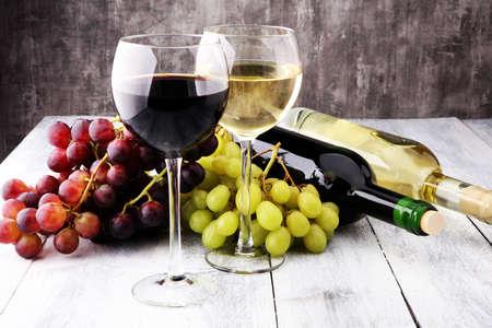 木製の背景のブドウのワイングラス。赤と白のワインのコンセプト