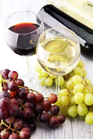 Glasses of wine and grapes on wooden background. red and white wine concept