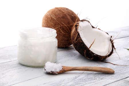 Coco y frasco de vidrio abierto con aceite de coco fresco sobre fondo de madera. Foto de archivo