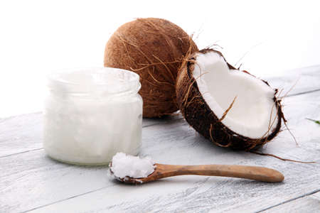 coconut and opened glass jar with fresh coconut oil on wooden background.