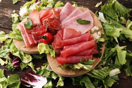 Food tray with delicious salami, pieces of sliced ham, sausage, tomatoes, salad and vegetable - Meat platter with selection Stock Photo - 93952615